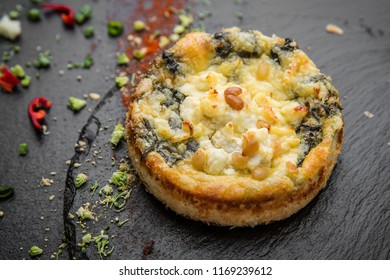 Traditional mini quiche pie with feta, spinach and pine nuts.