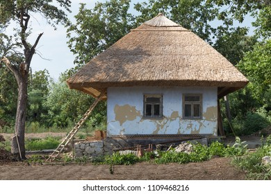 Traditional moldovian rural house. House is under roofing from bulrush and an old pear.