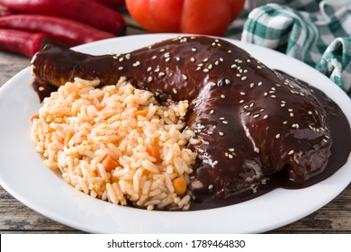 Traditional mole Poblano with rice in plate on wooden table