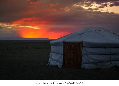 Traditional Mongolian housing / yurt at sunset with dramatic cloudy sky in the Gobi Desert near the Flaming Cliffs (Bajandsag, Gobi Desert, Mongolia, Asia)