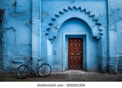 Traditional Moroccan ancient wooden entry door. In the old Medina in Chefchaouen, Morocco. Typical, old, blue intricately carved, studded, Moroccan riad door.