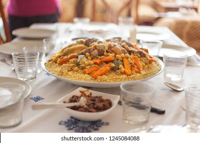 Traditional Moroccan couscous on a table on a house dinning room with empty glasses, caramelized onion with raisins, cutlery and empty dishes. Family holiday meeting ready table concept.
