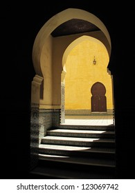 Traditional Moroccan doorway with stairs, shadow and yellow wall. Meknes. Tomb of Moulay Ismail.