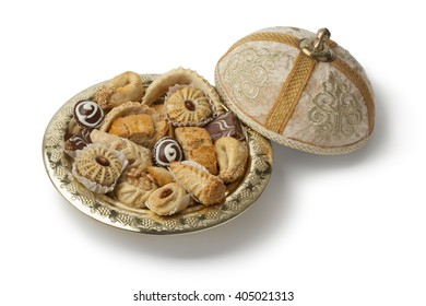 Traditional Moroccan festive cookies on a metal tajine on white background