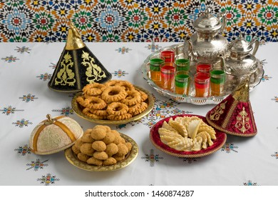 Traditional Moroccan homemade cookies in festive metal tajines on an embroidered tablecloth
