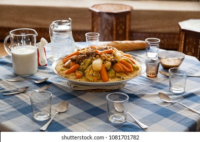 Traditional Moroccan homemade Couscous plate on a blue squared clothed table served with a moroccan living room on the background with glasses spoons and Laban milk . Morocco family gathering concept.