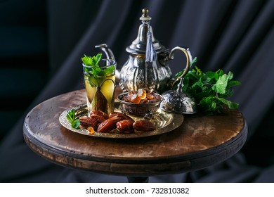 Traditional moroccan mint tea with copper teapot, dates and sugar