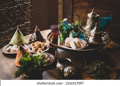 Traditional moroccan mint tea with teapot, sweets and sugar. Vintage editing
