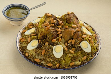 Traditional Moroccan Rfissa dish with eggs, almonds and a bowl with sauce