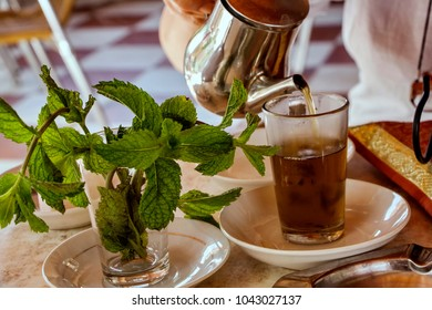 Traditional Moroccan tea served with fresh mint ona  silver plate.