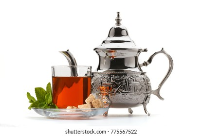 Traditional moroccan teapot with glass of green tea isolated on white background