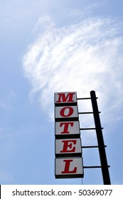 """Traditional """"Motel"""" sign against a cloud in the sky"""