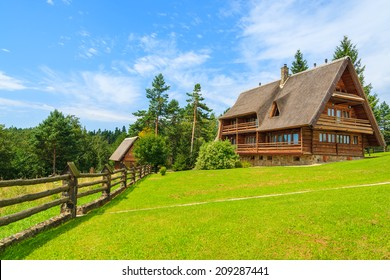 Traditional mountain house on green field in a village near Arlamow, Bieszczady Mountains, Poland