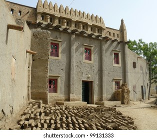 Traditional mud brick dwelling in the West African nation of Mali. Mud bricks are drying under the sun in the foreground.