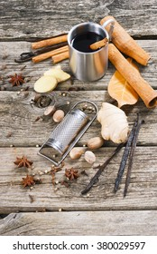 traditional mulled wine in purity steel mug and grater, spices on old wooden table