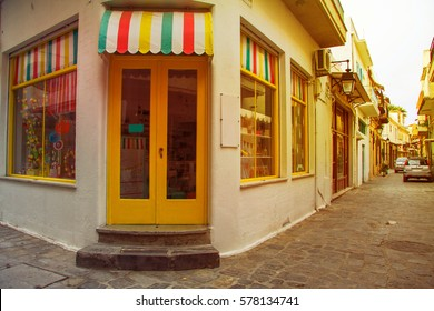 Traditional multicolor facade of shop from the street greek island town panorama. Image with sunkissed effect, toned