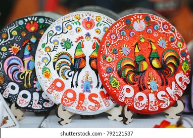 Traditional multi-colored souvenir ceramic plates on the stands at local souvenir shop under the open sky in Poland, Krakow.