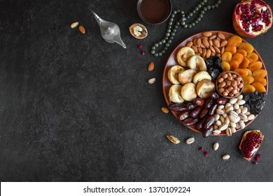 Traditional Muslim Iftar Food on black, copy space. Ramadan kareem with dates, nuts, dried fruits and coffee. Ramadan iftar food concept with rosary.