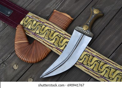 Traditional muslim islamic dagger from Yemen called jambiya with steel blade and a horn handle, and golden embroidered belt