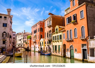 Traditional narrow canal with gondolas in Venice, Italy