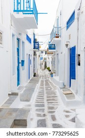 Traditional narrow street in Mykonos with blue doors and white walls.