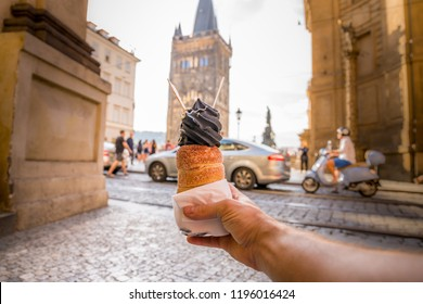 Traditional national Czech sweet food Trdelnik filled with ice cream and Charles bridge tower in the background