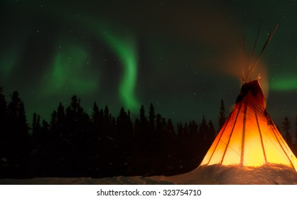 Traditional native dwelling in the far north with northern lights in the sky.