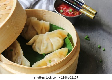 Traditional Nepali Homemade Steamed  Momos in Bamboo steamer with Tomato dip close up, selective focus