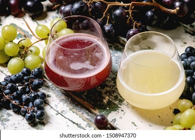 Traditional New european low alcohol red and white wine Federweisser or Neuer Wein, Burcak, Vin bourru in glasses with black and green grapes bunches on old white wooden table.