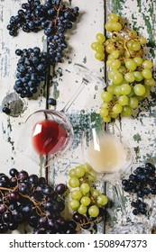 Traditional New european low alcohol red and white wine Federweisser or Neuer Wein, Burcak, Vin bourru in lying glasses with black and green grapes bunches over old wooden background. Flat lay, space