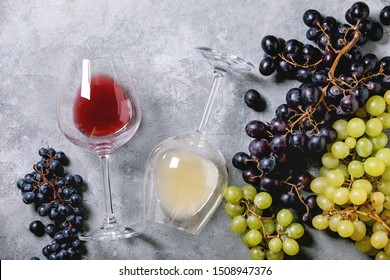 Traditional New european low alcohol red and white wine Federweisser or Neuer Wein, Burcak, Vin bourru in lying glasses with black and green grapes over grey concrete background. Flat lay, space