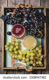 Traditional New european low alcohol red and white wine Federweisser, Neuer Wein, Burcak, Vin bourru in glasses, black and green grapes bunches in wood tray over old wooden background. Flat lay, space
