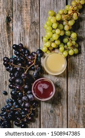 Traditional New european low alcohol red and white wine Federweisser or Neuer Wein, Burcak, Vin bourru in glasses with black and green grapes bunches over old wooden background. Flat lay, space