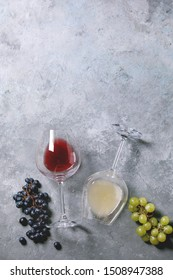 Traditional New european low alcohol red and white wine Federweisser or Neuer Wein, Burcak, Vin bourru in lying glasses with black and green grapes over grey concrete background. Flat lay, copy space