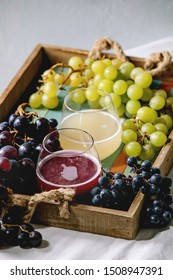 Traditional New european low alcohol red and white wine Federweisser or Neuer Wein, Burcak, Vin bourru in glasses with black and green grapes bunches in wooden tray on white table cloth. Copy space.