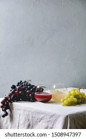 Traditional New european low alcohol red and white wine Federweisser or Neuer Wein, Burcak, Vin bourru in glasses with black and green grapes bunches on white table cloth. Copy space.