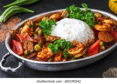 Traditional New Orleans seafood gumbo with fried sausages, shrimps, vegetables (okra, green peas, bell peppers), roux and Cajun spices, served with white rice