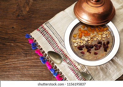 Traditional Noah's pudding, ashura, ashure in an old copper bowl, authentic table cloth, old spoon,  wooden table, space for text
