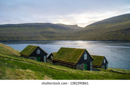 Traditional nordic Scandinavian village houses with green grass roof. Iconic scenic view of Faroe Island, Denmark, Europe. Beautiful tourist spot located at Vágar Island. Moody weather scene.