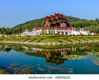 The traditional norther Thai style pavilion with its reflections on the water of a moat in the botanical garden in Chieng Mai, Thailand with blur background of mountain from afar under the sun
