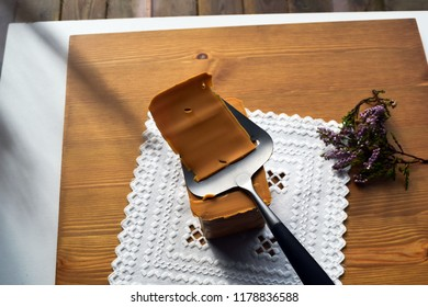 Traditional Norwegian brown cheese on a white napkin with embroidery hardanger. Brunost. Sheep cheese. A piece of soft brown caramel cheese and a slicer on a wooden surface.