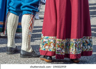 "Traditional norwegian clothing called a ""bunad"". The lady has embroidered a part if the bayeux tapestry on her dress and the man has long knitted woolen socks"
