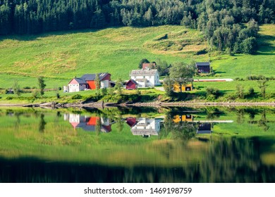 Traditional Norwegian summer farm along lake Vangsvatnet reflected in the water near Voss Hordaland county Norway