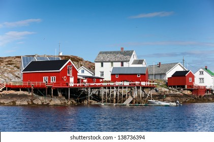 Traditional Norwegian village with red and white wooden houses on rocky coast