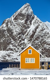 traditional norwegian wooden house rorbu to stand on the shore of the fjord and mountains in the distance. Lofoten Islands. Norway. world travel