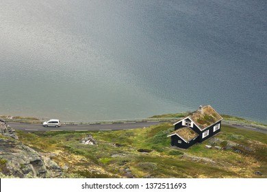 Traditional norwegian wooden house. Typical Norwegian house near lake. Typical norwegian house with grass on the roof. Norwegian typical grass roof country house. Tourism holidays and travel.