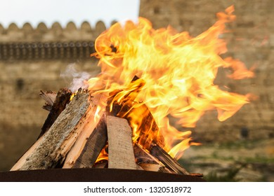 Traditional Novruz holiday bonfire with old brick palace wall as background, close-up.
