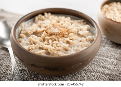 Traditional oatmeal breakfast bowl with milk and sugar