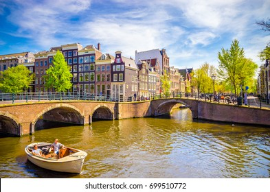 Traditional old buildings and and boats in Amsterdam, Netherlands. Canals of Amsterdam.