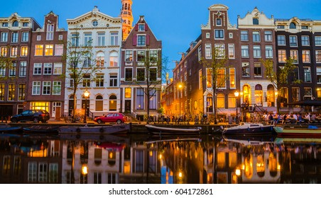Traditional old buildings and boats at night in Amsterdam, Netherlands